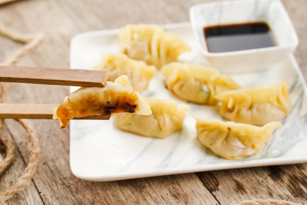 White plate of dumplings in background with chopstick holding dumpling in front