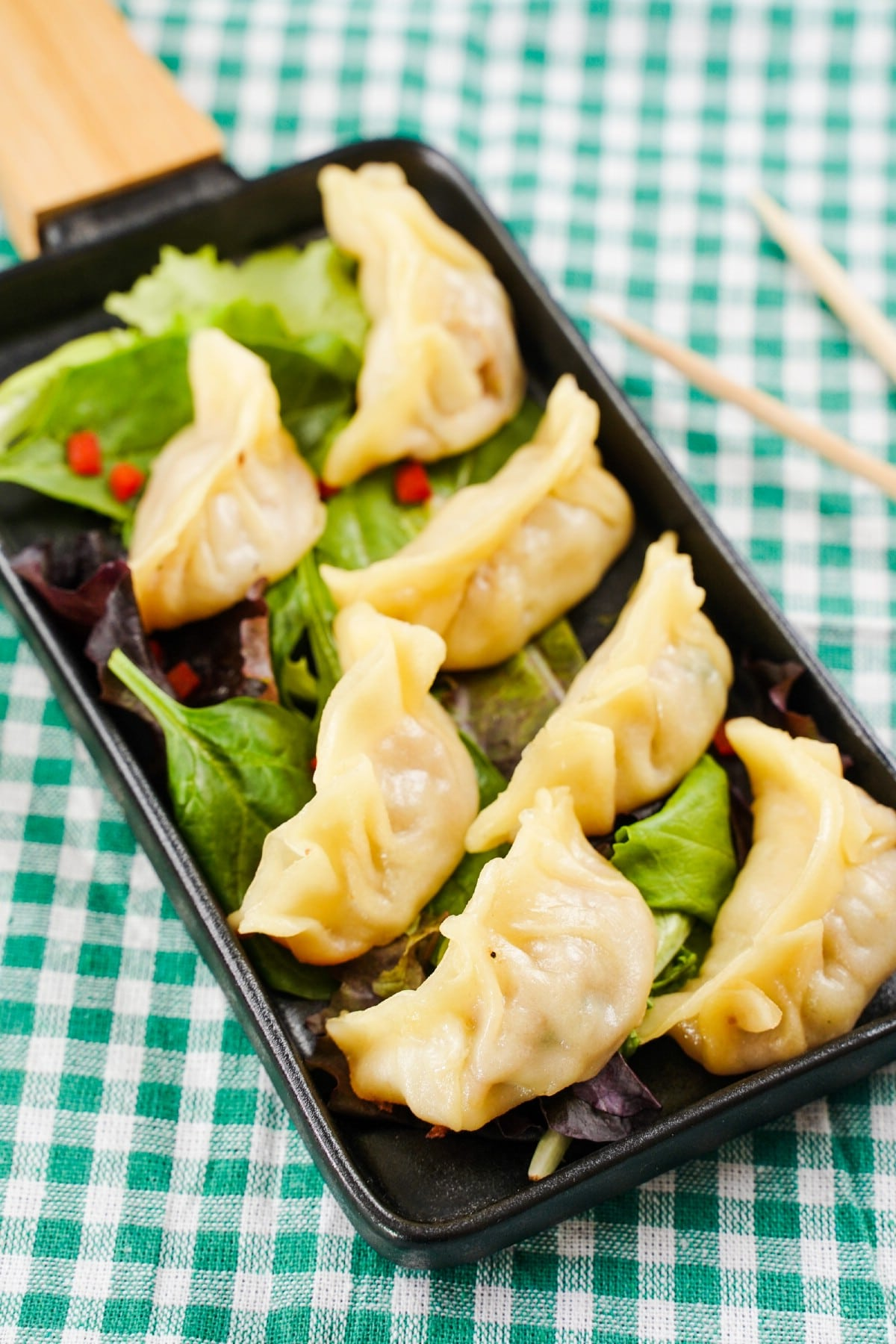 Long black tray of dumplings on green and white tablecloth