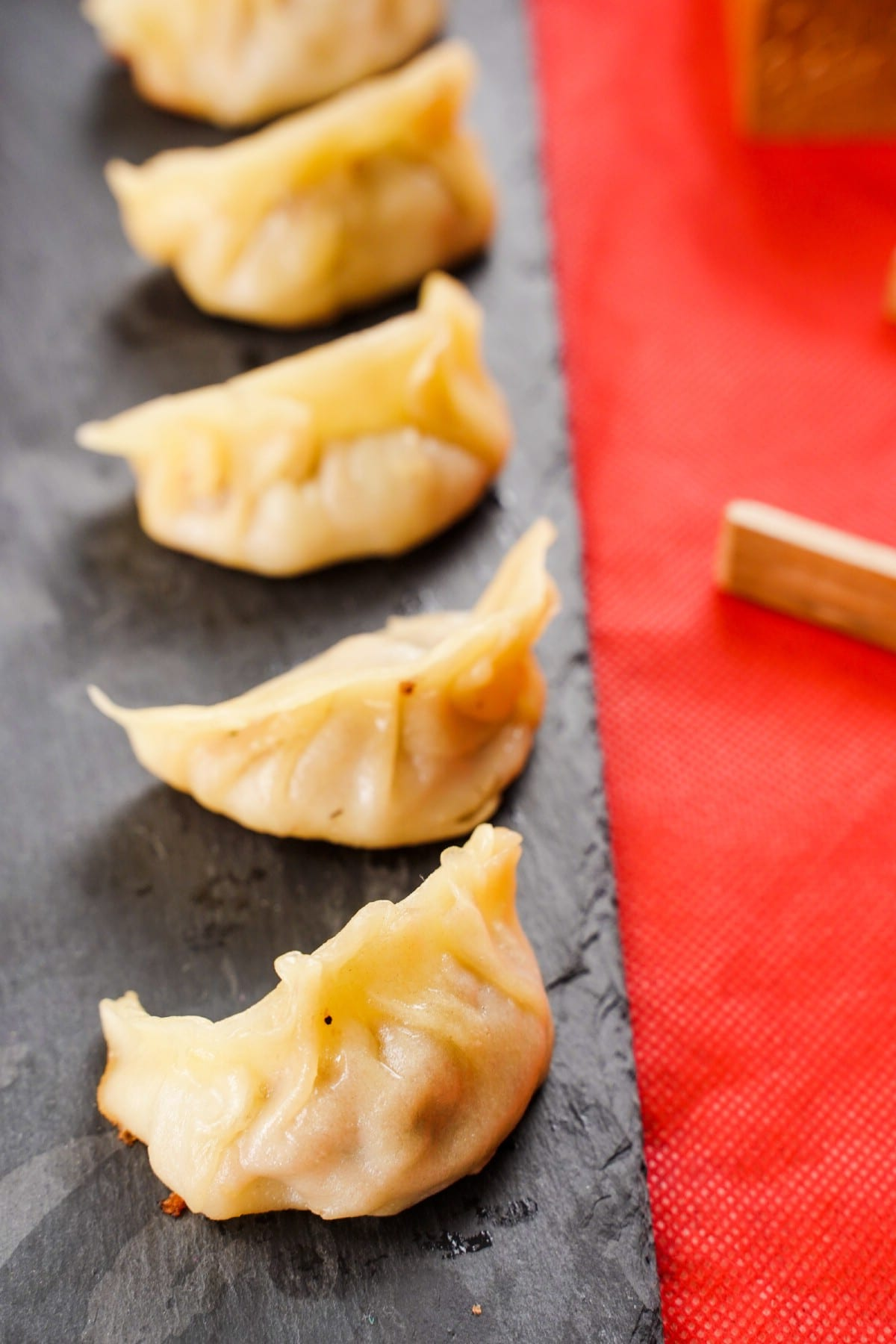 Black slate on red table topped with line of cooked dumplings
