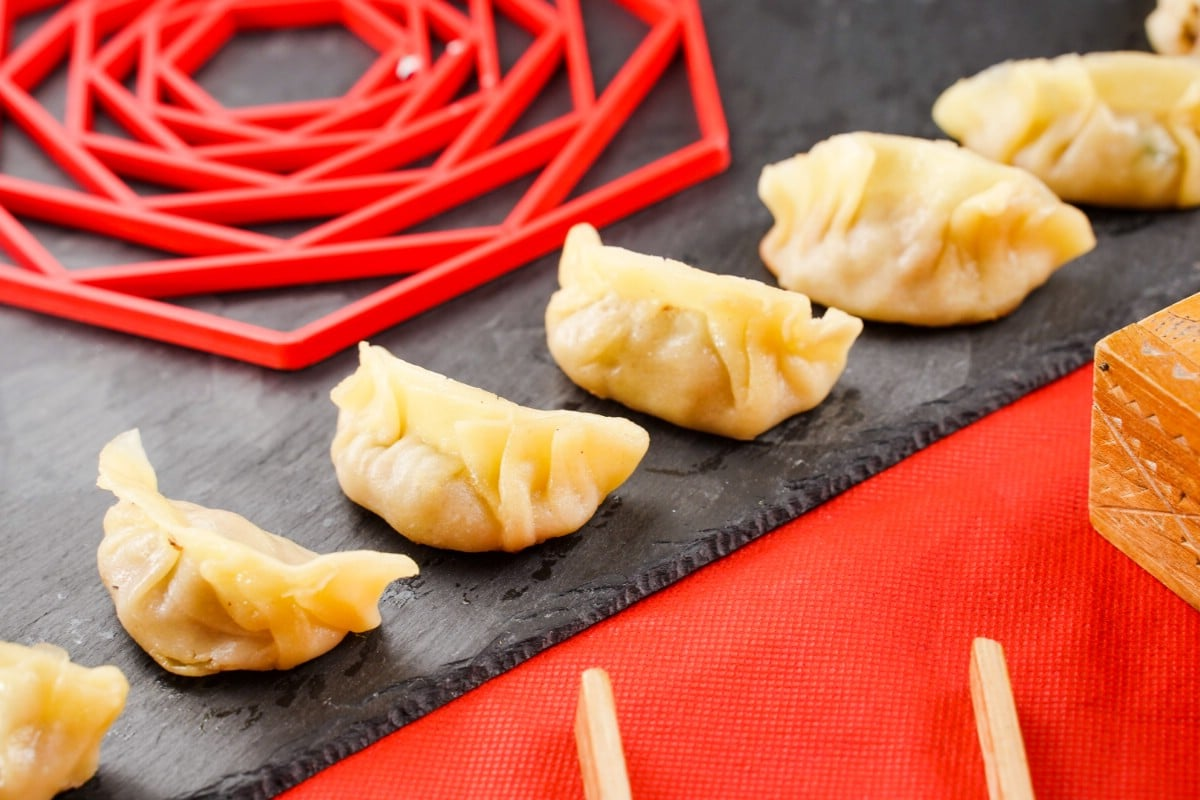 Cooked pork dumplings lined up on black tray sitting on red table