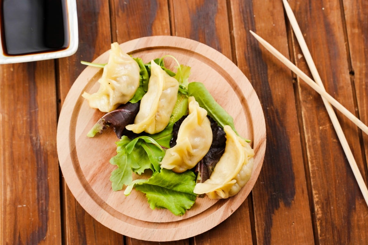 Round board with dumplings on top by chopsticks and square bowl of soy sauce