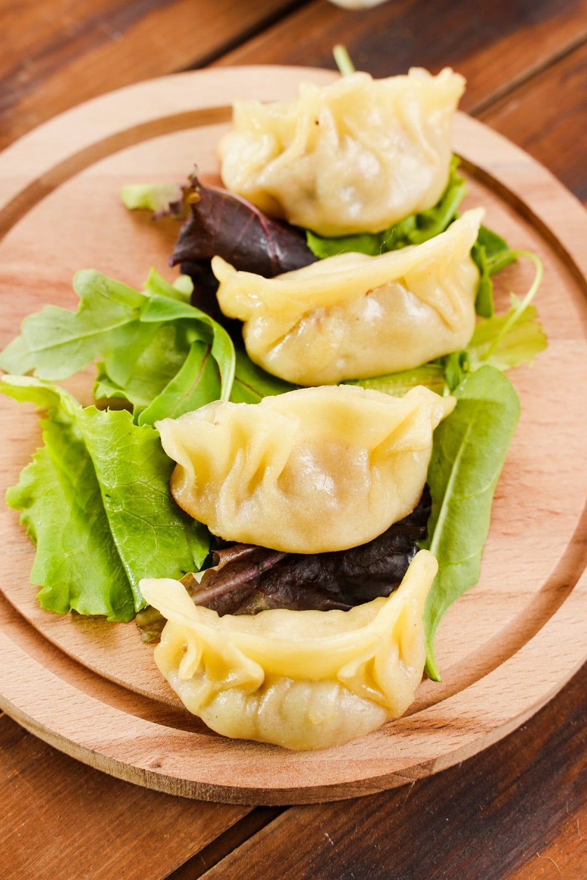 Image from overhead of dumplings on round board sitting on table