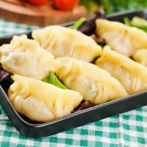Dumplings on black plate sitting on green checked tablecloth
