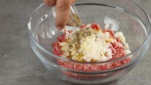 Seasoning being added to glass bowl of meat