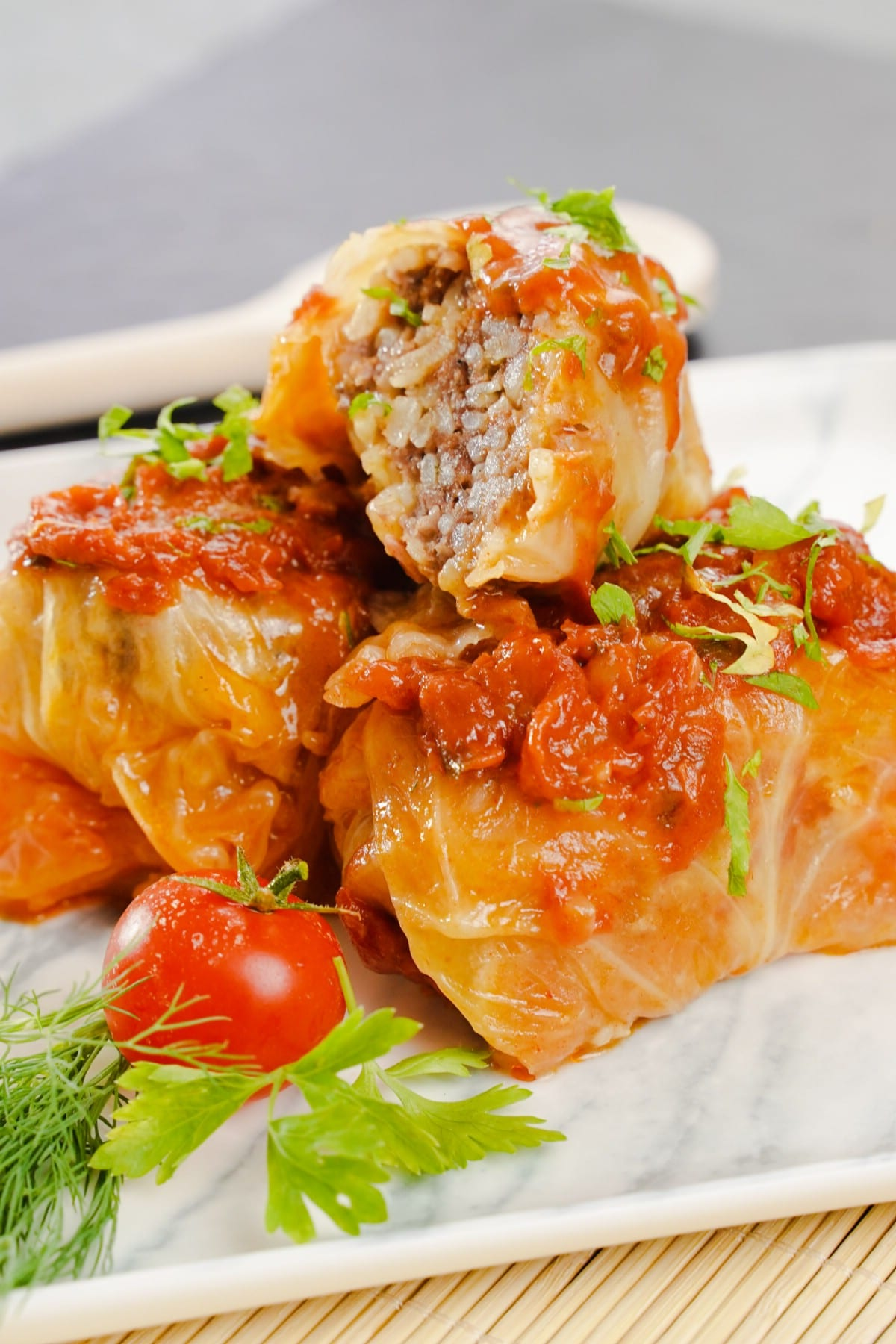 Stack of sarma rolls on white plate with greens and tomato