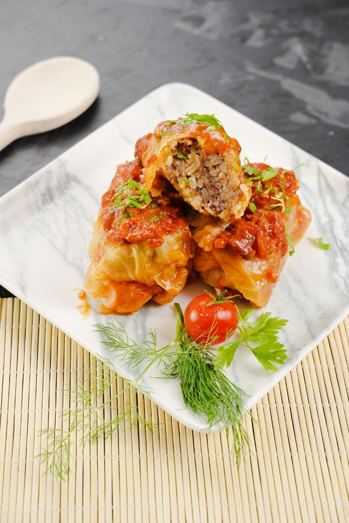 Square marble plate with stack of sarma and fresh herbs on black table