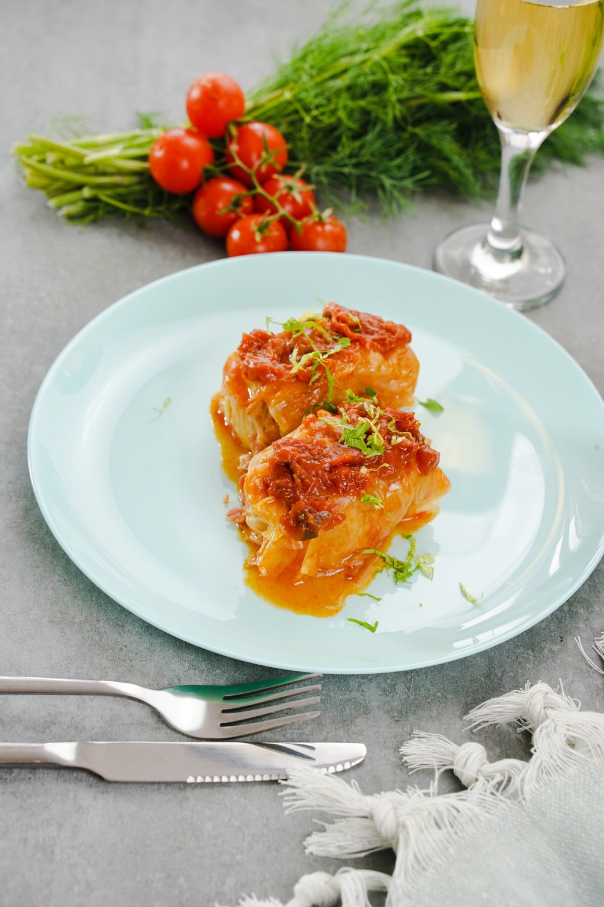 White plate of cabbage rolls by fresh tomatoes and wine glass