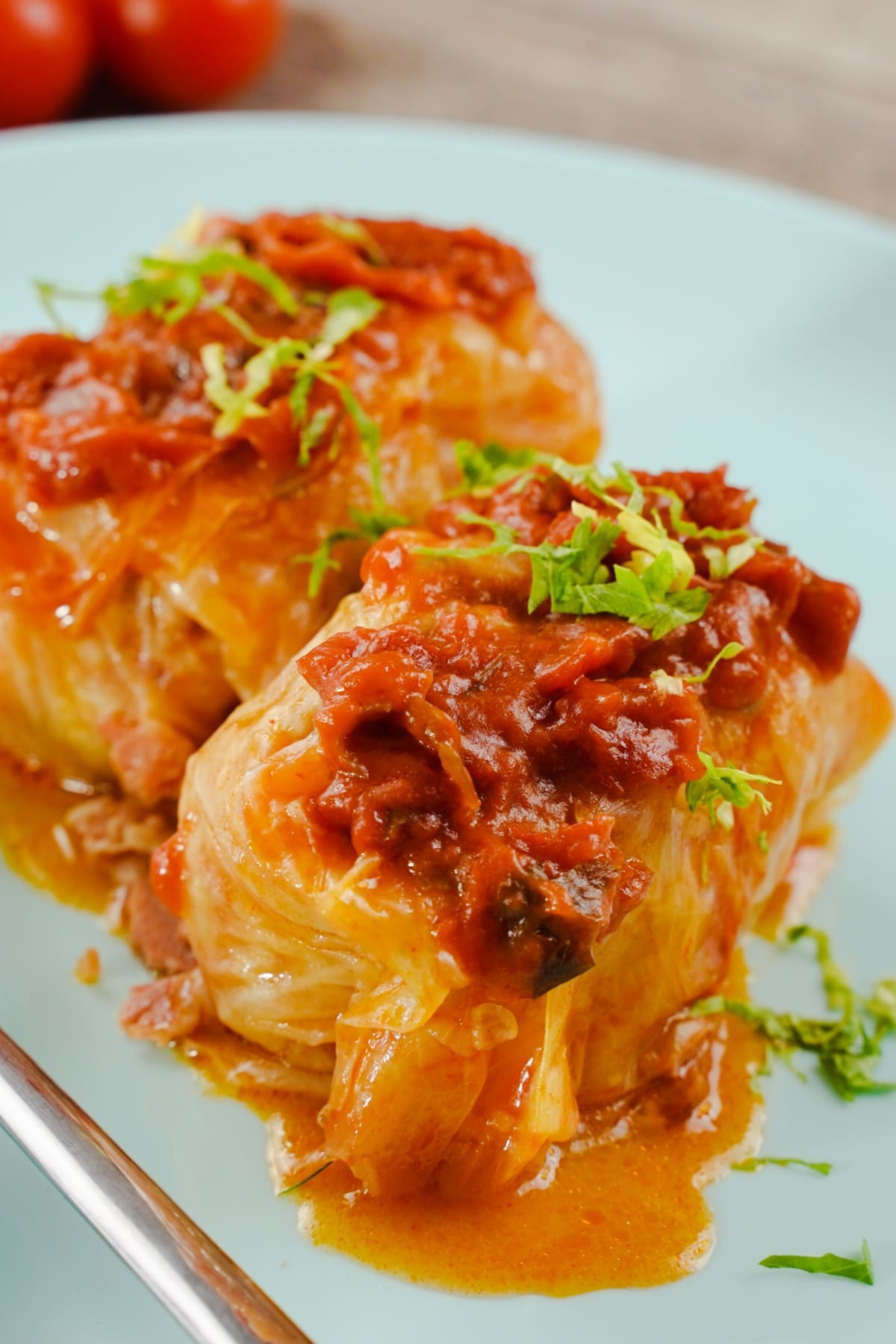 Close up image of white plate of stuffed cabbage with red sauce on top