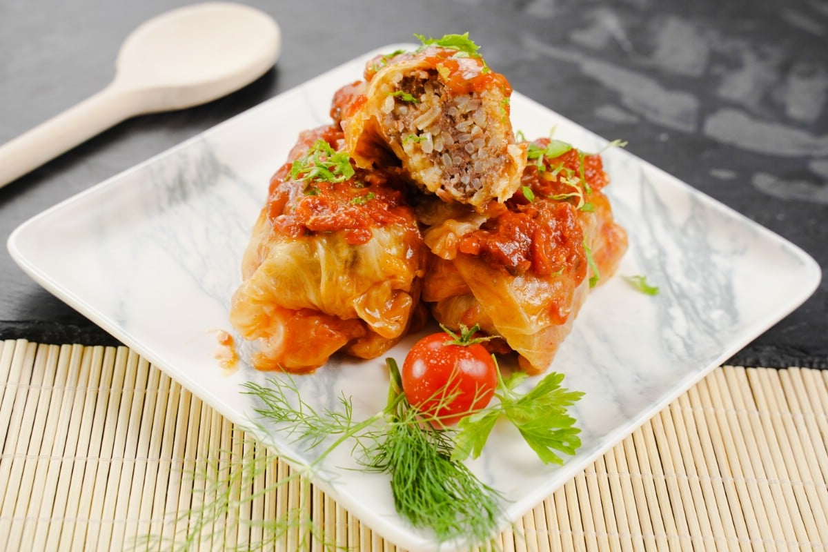 Square white plate on bamboo mat with stack of cabbage rolls on top