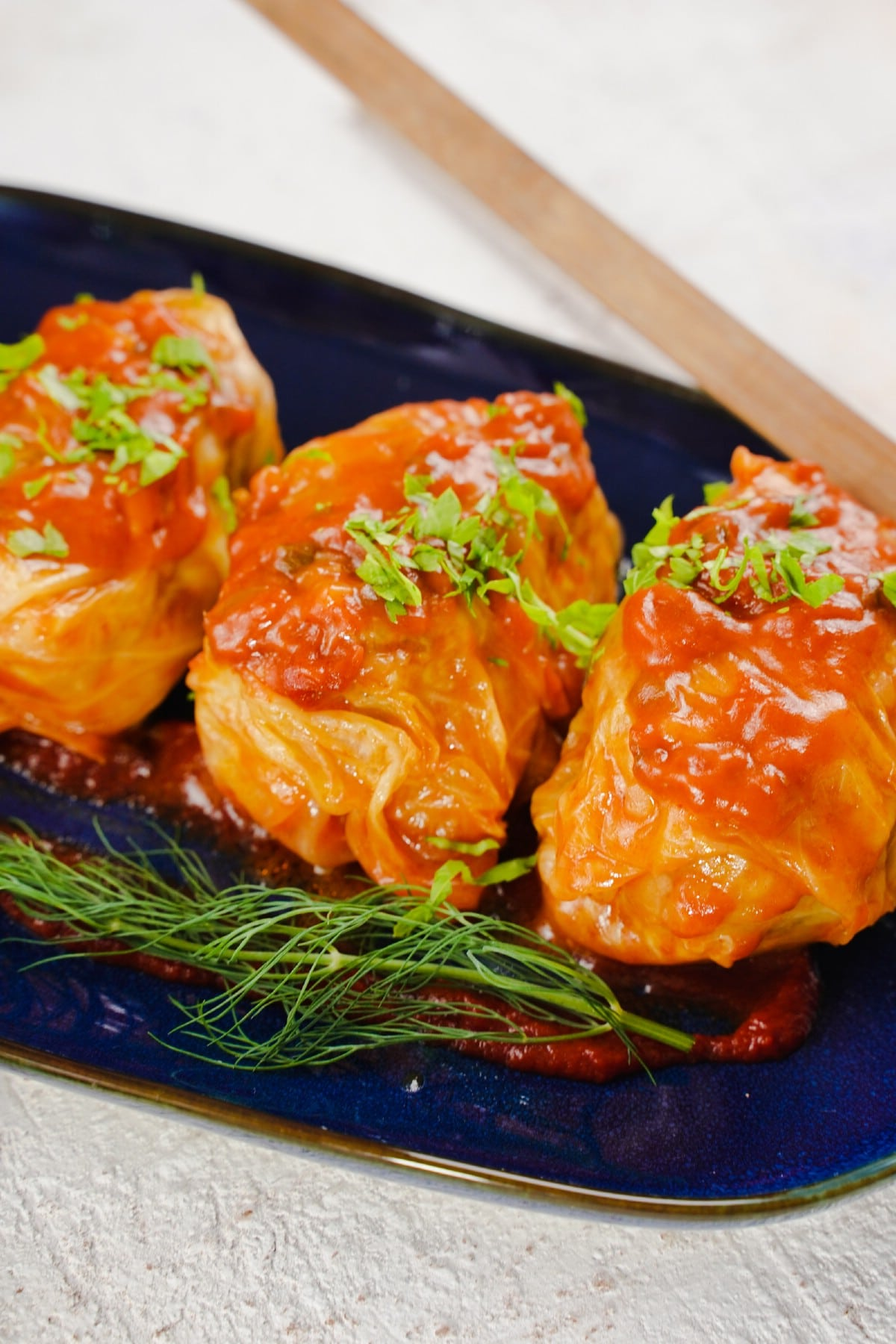 Blue platter of sarma on white table topped with fresh herbs