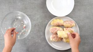 Plate of stuffed cabbage rolls on gray table
