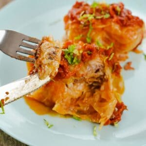 Fork and knife holding up bite of cabbage roll