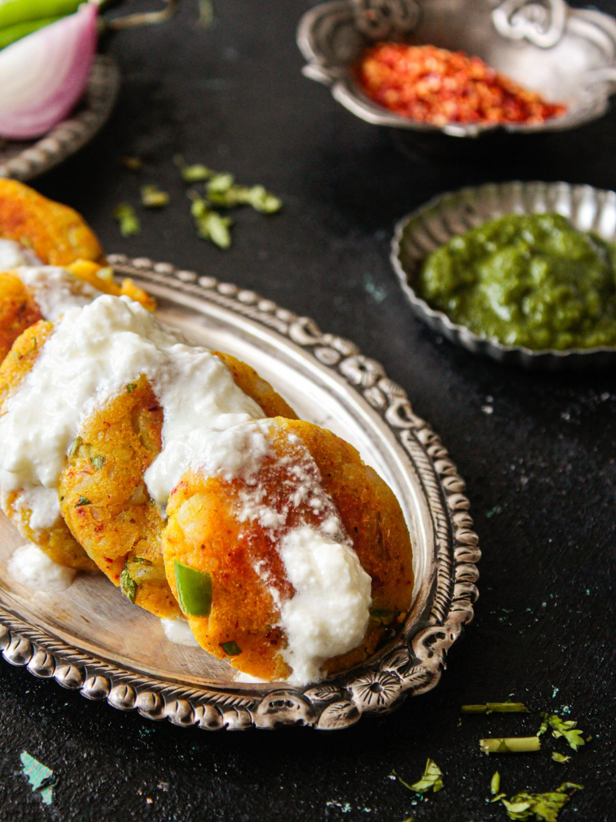 Plate of aloo tikki with curd on top