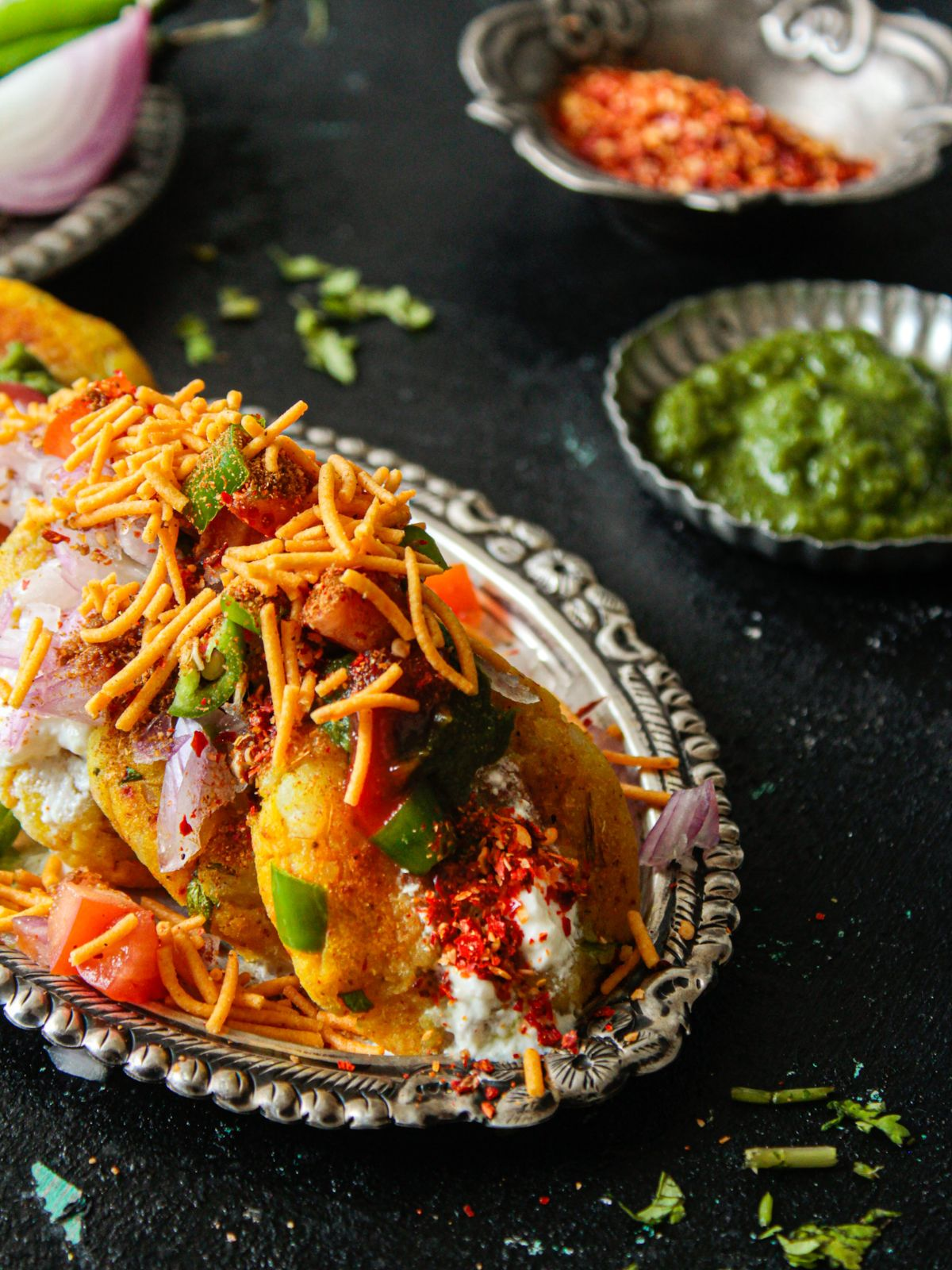 Silver platter topped with aloo tikki chaat on black table