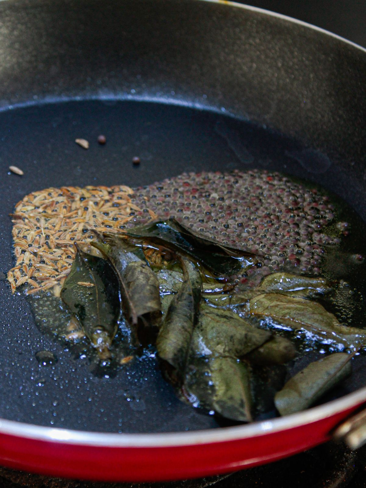 Curry leaves in skillet with ghee