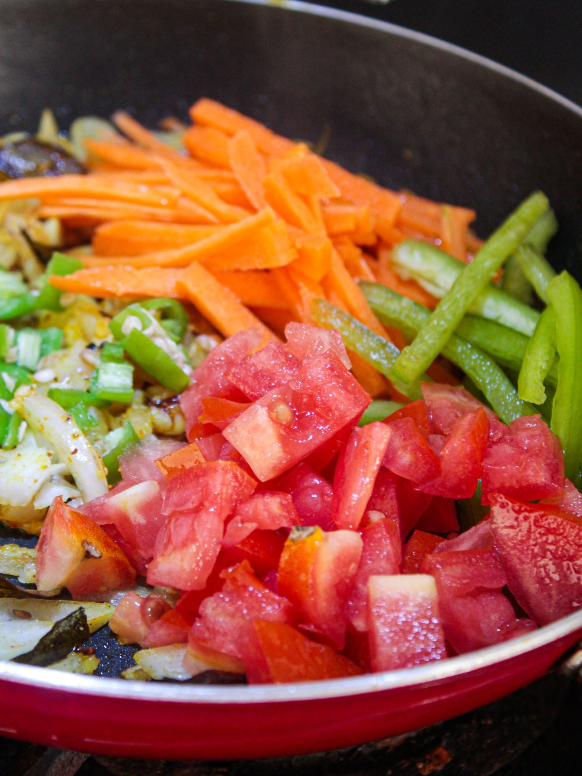 Carrots peppers and tomatoes in large red skillet
