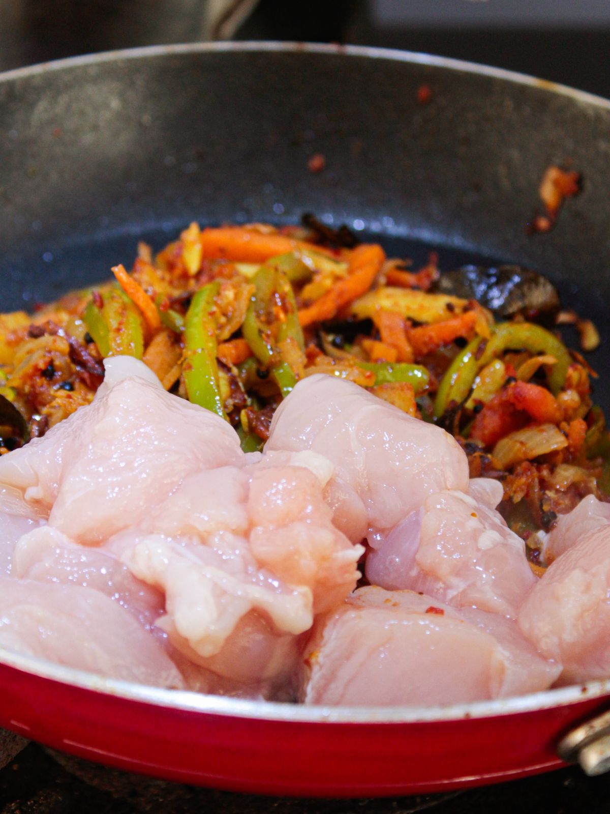 Raw chicken in skillet by vegetables