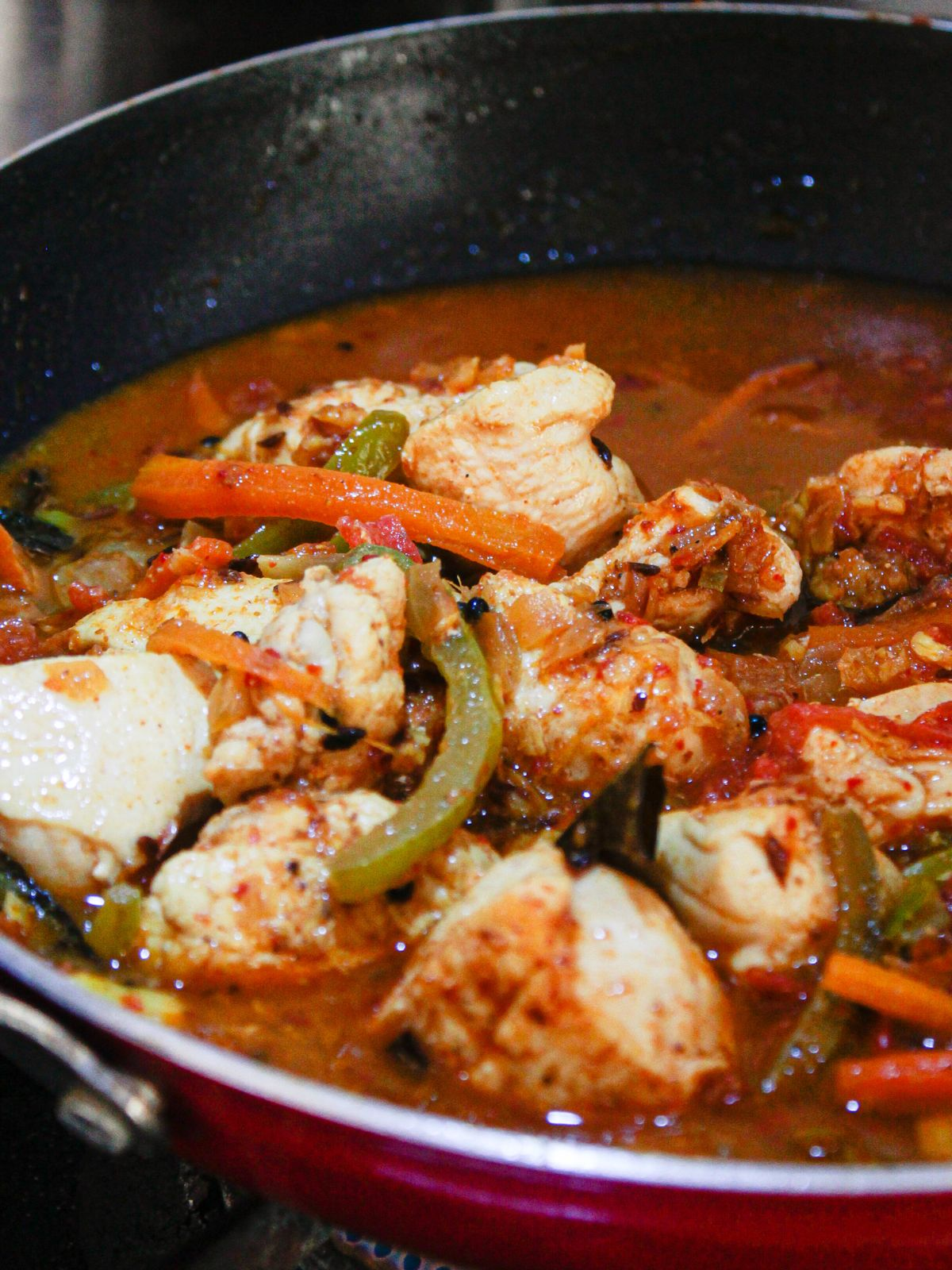Chicken and vegetables in skillet with red sauce