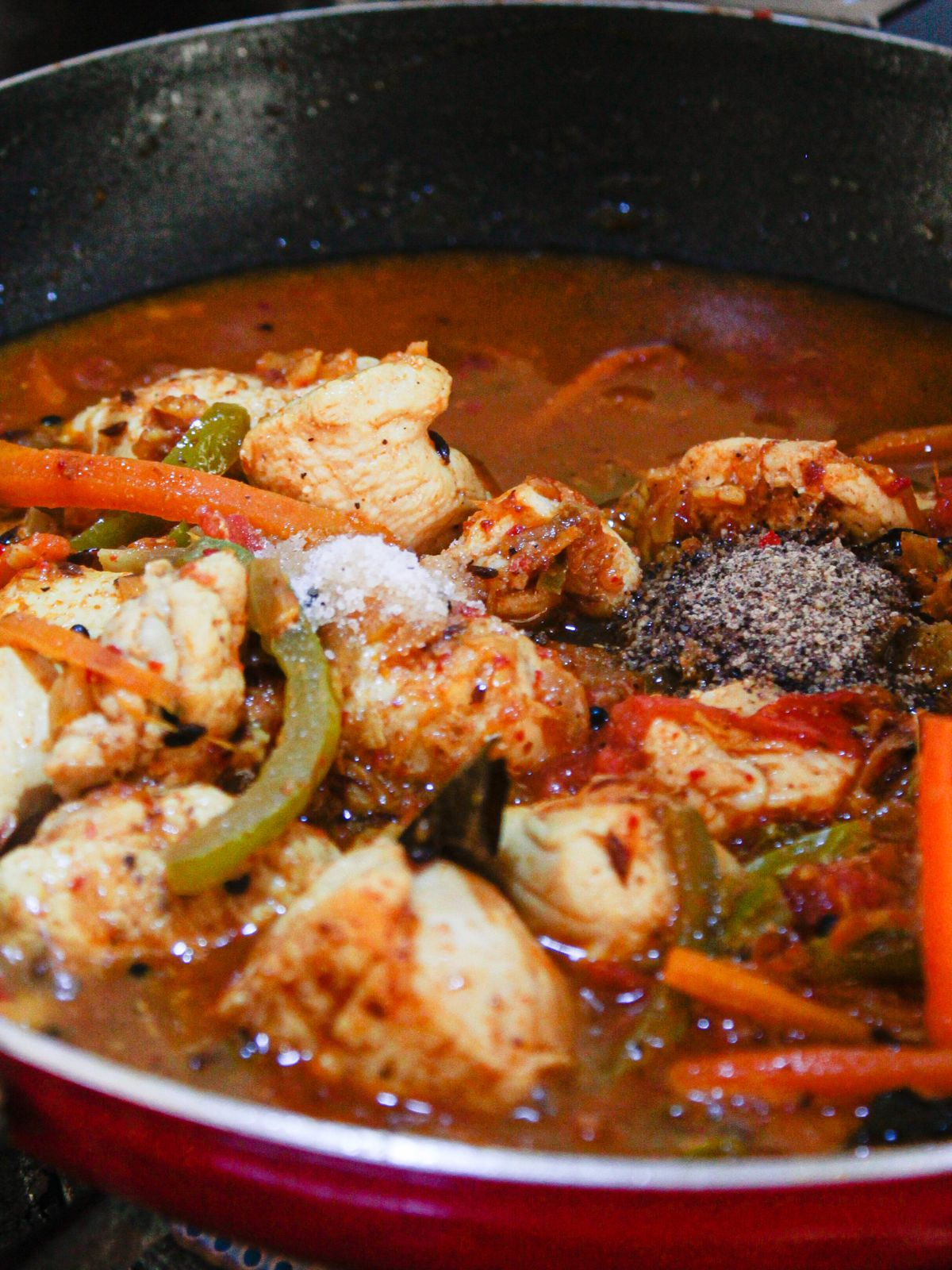 Spices on top of chicken jalfrezi being cooked in red skillet