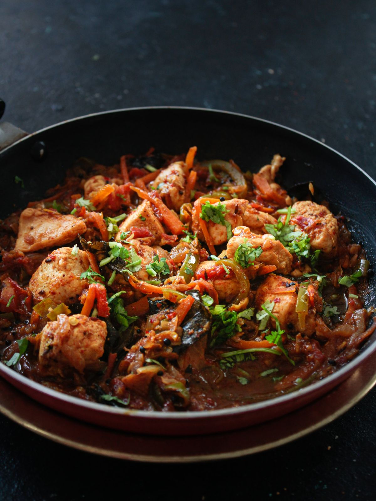 Red skillet of chicken stir fry sitting on black table