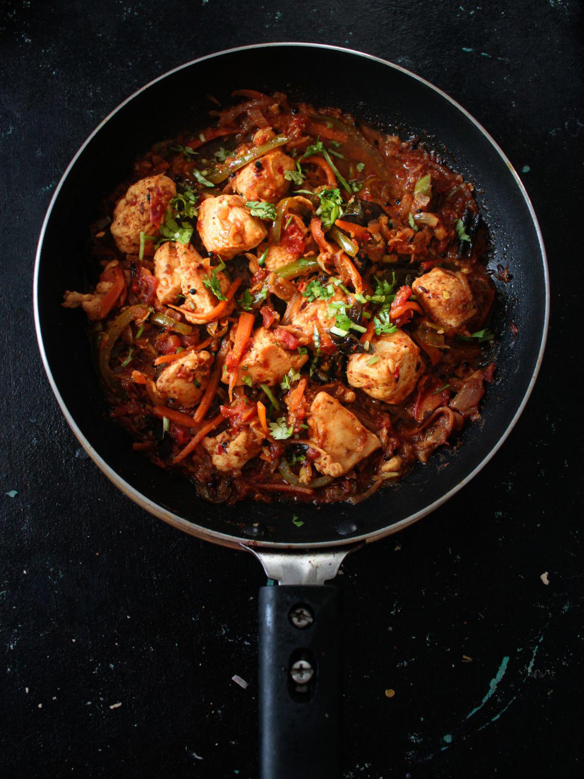 Chicken Jalfrezi in skillet on black table