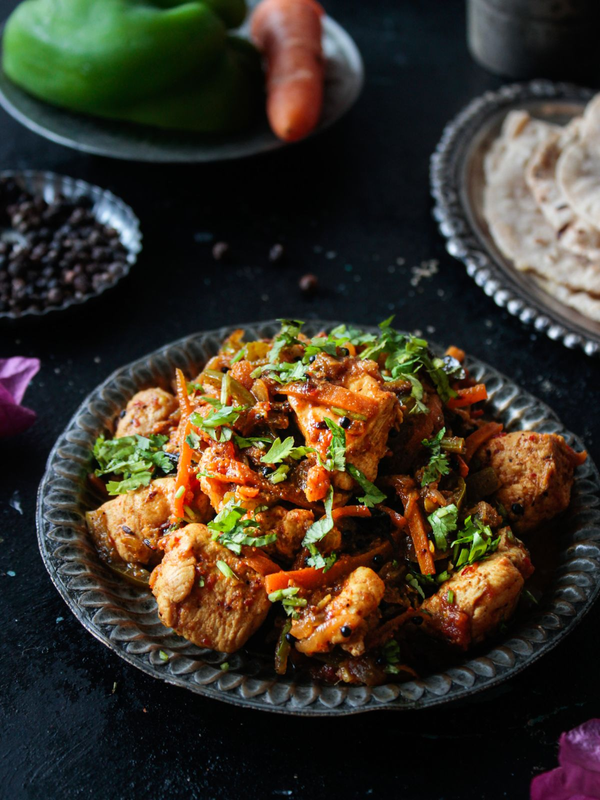 Black plate of chicken with vegetables on black table next to plate of naan
