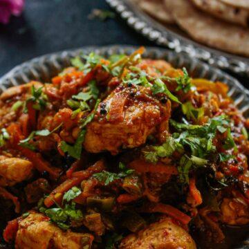 Chicken Jalfrezi in round black plate next to naan