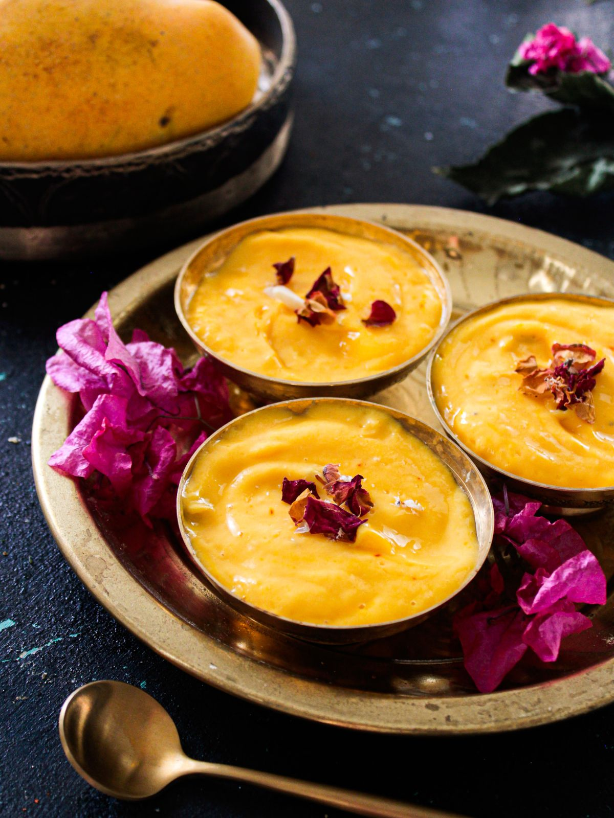 Mango shrikhand topped with rose petals in small gold bowls next to pink flowers