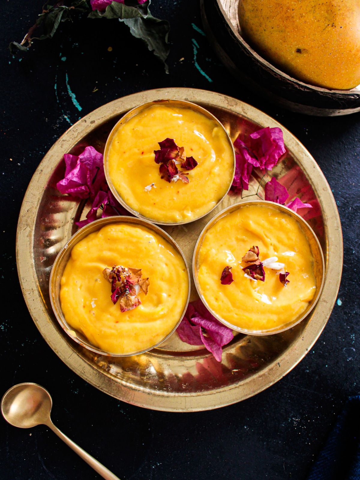 Three small gold bowls filled with mango shrikhand sitting in round gold platter on black table