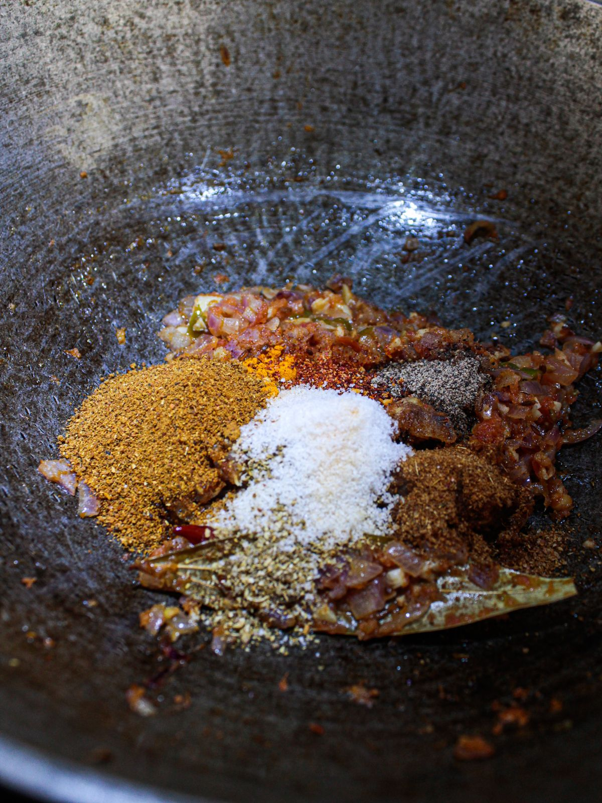 Spices sprinkled over top of onion and tomato puree in skillet