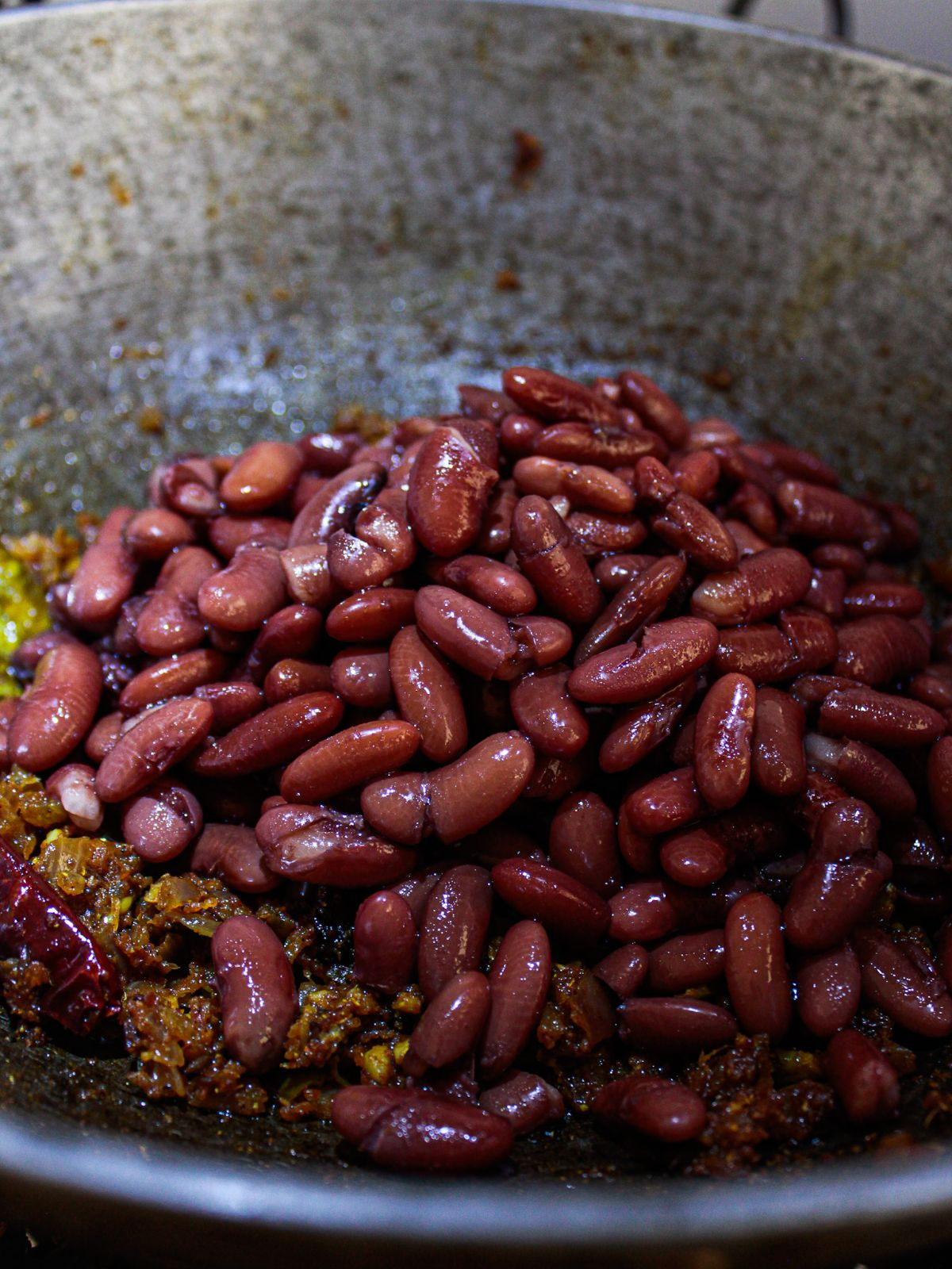 Kidney beans on top of curried spices and onions