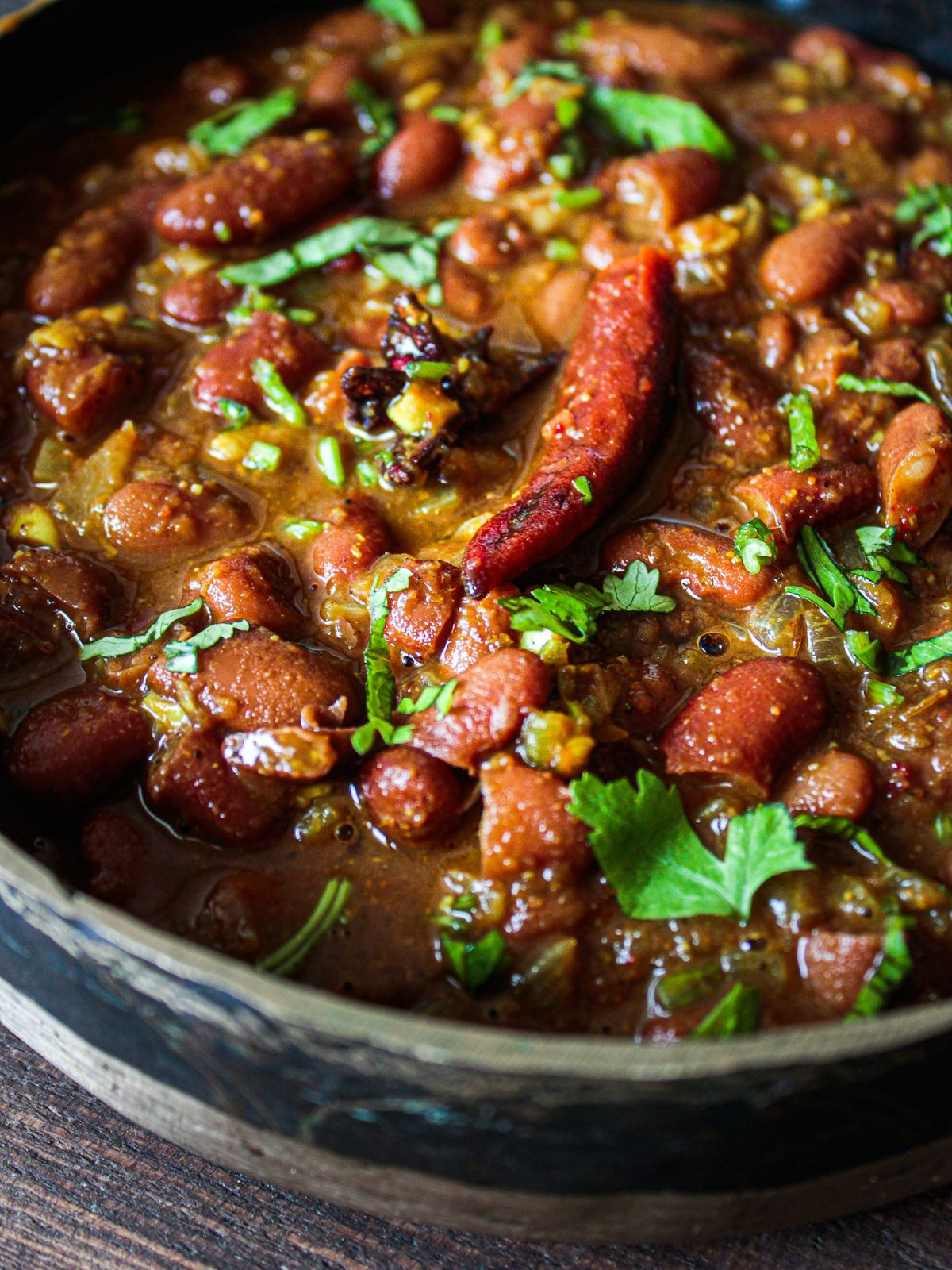 Large bowl of bean curry topped with cilantro on wood table