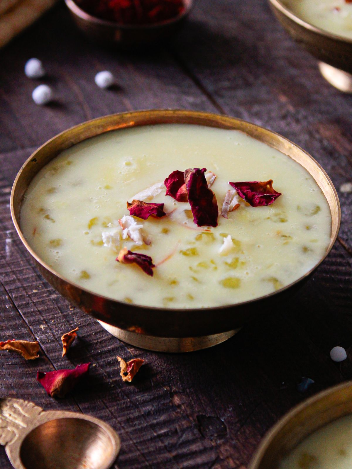 Gold bowl on table filled with tapioca kheer topped with rose petals
