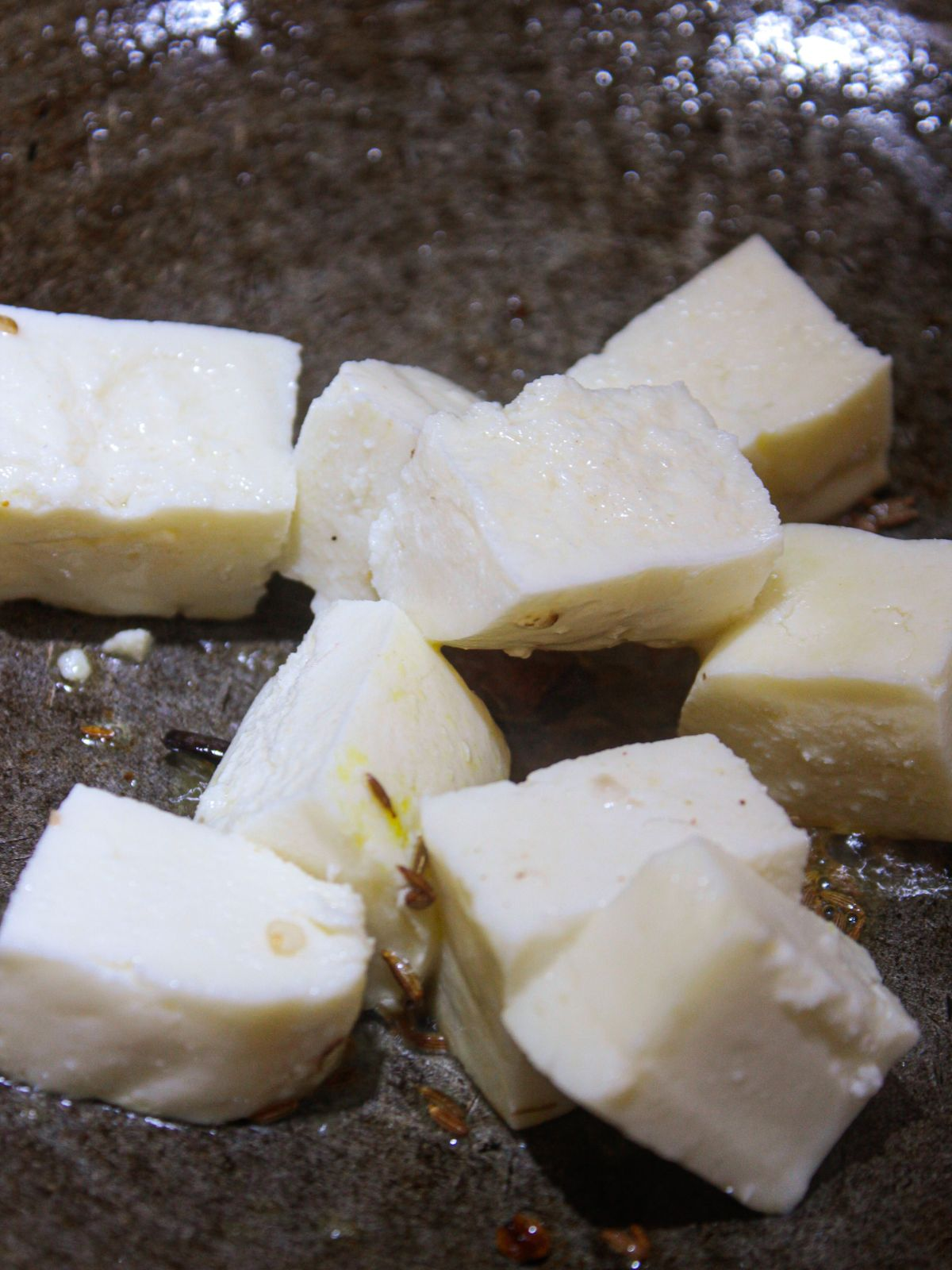 Paneer cubes in a skillet with oil