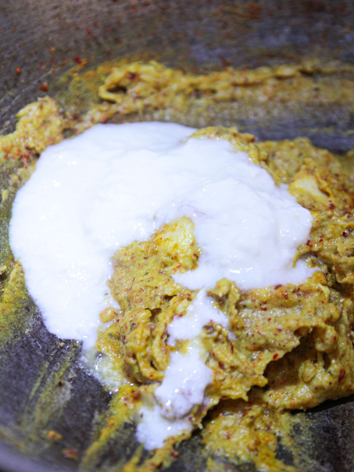 Yogurt poured over curry mixture in skillet