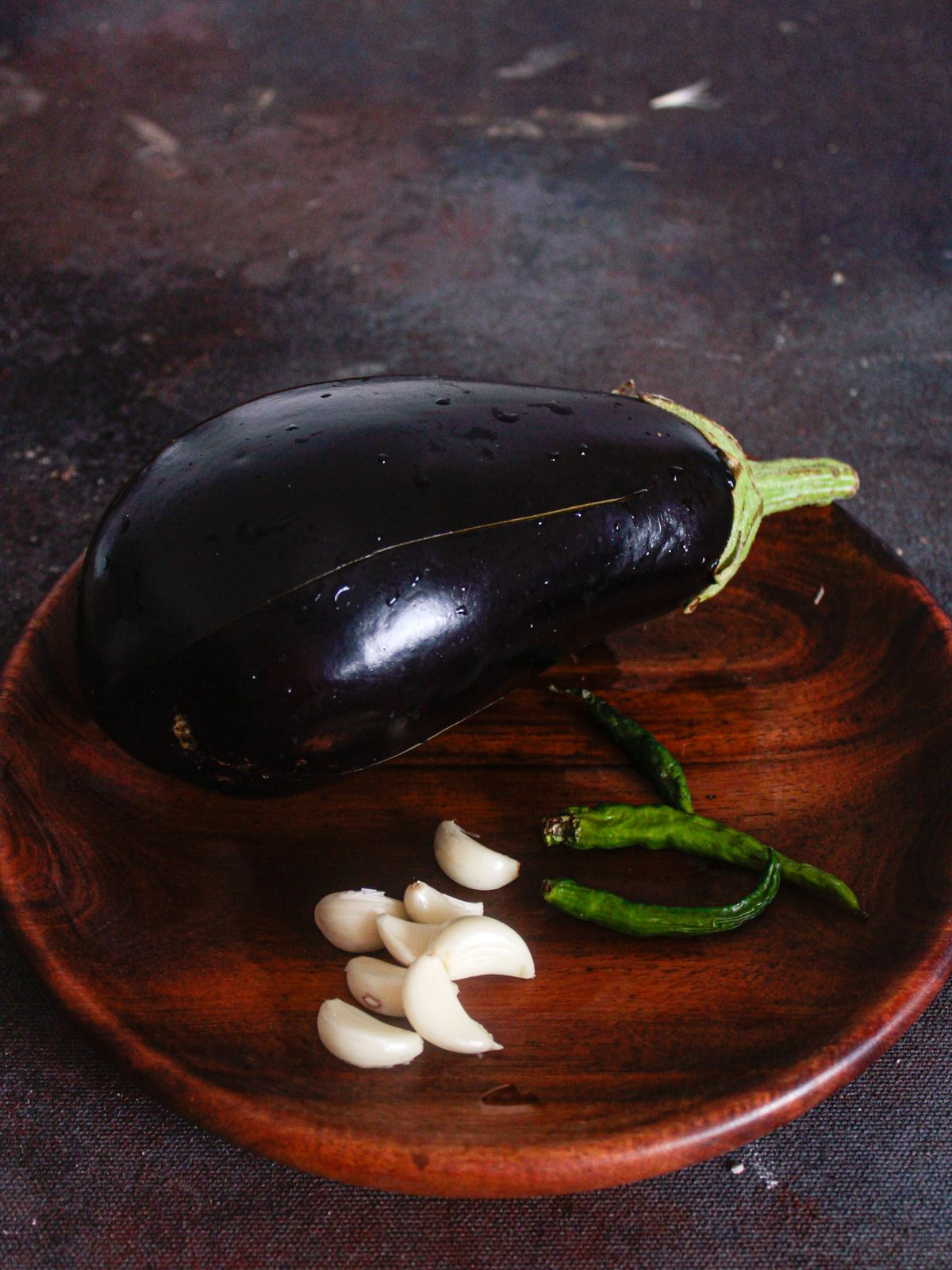 Wooden bowl holding eggplant, chiles, and garlic