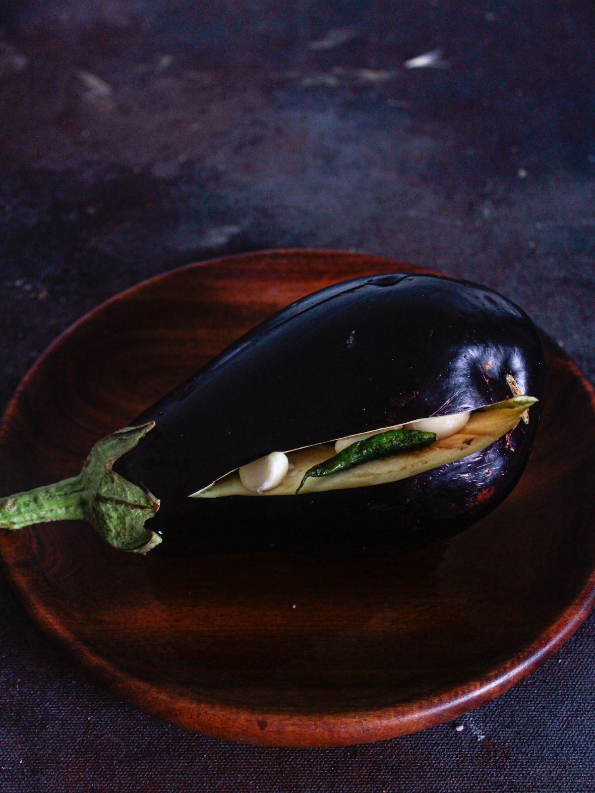 Wooden bowl with eggplant on top that has slit on side with chiles and garlic inside