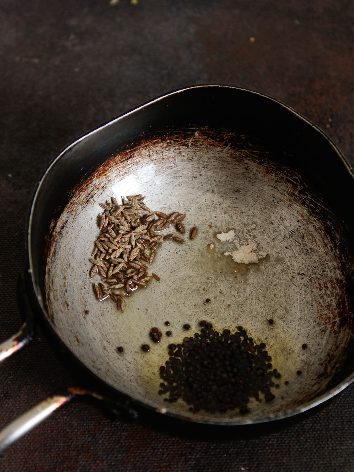 Mustard seeds cumin seeds and spices in oil in skillet