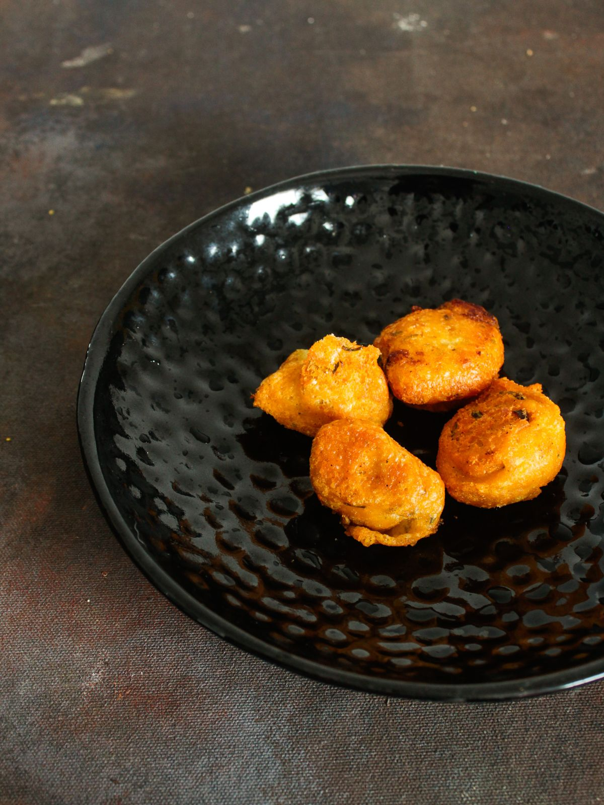 Bonda fritters in large blck bowl on gray tablecloth