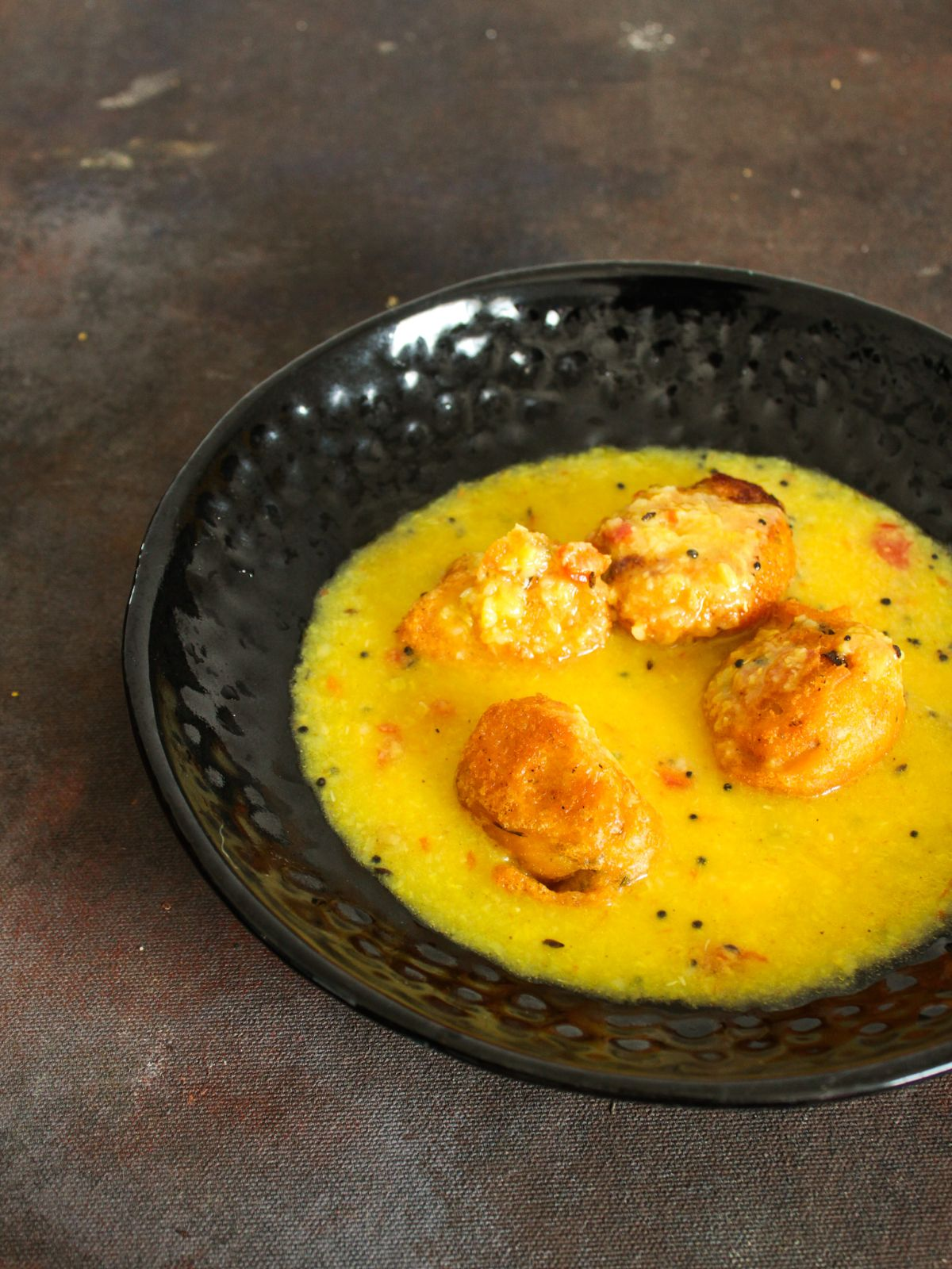 Yellow soup over lentil fritters