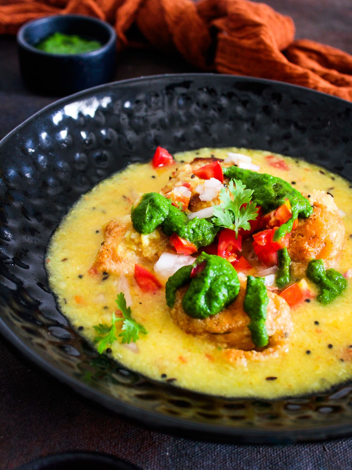 Black bowl of yellow soup with fritters in the middle topped by chutney and tomatoes