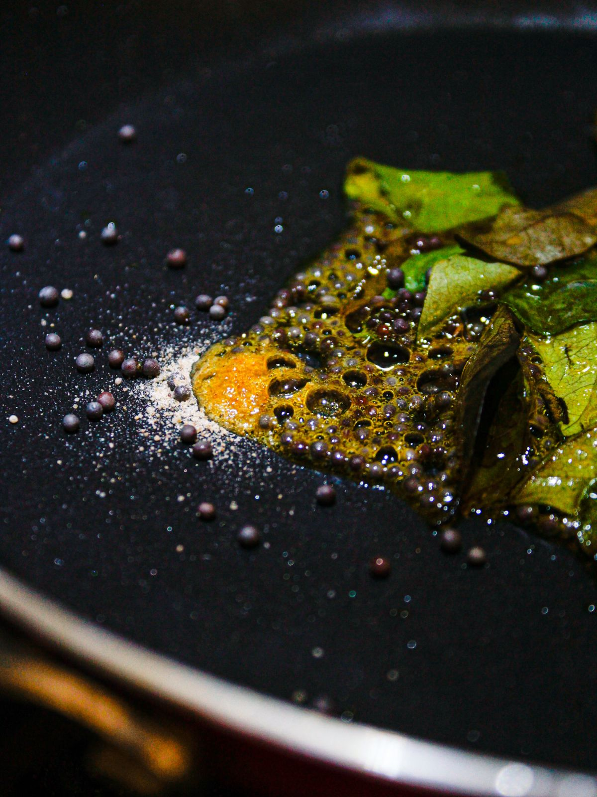 Seeds and chiles in hot oil in black skiillet