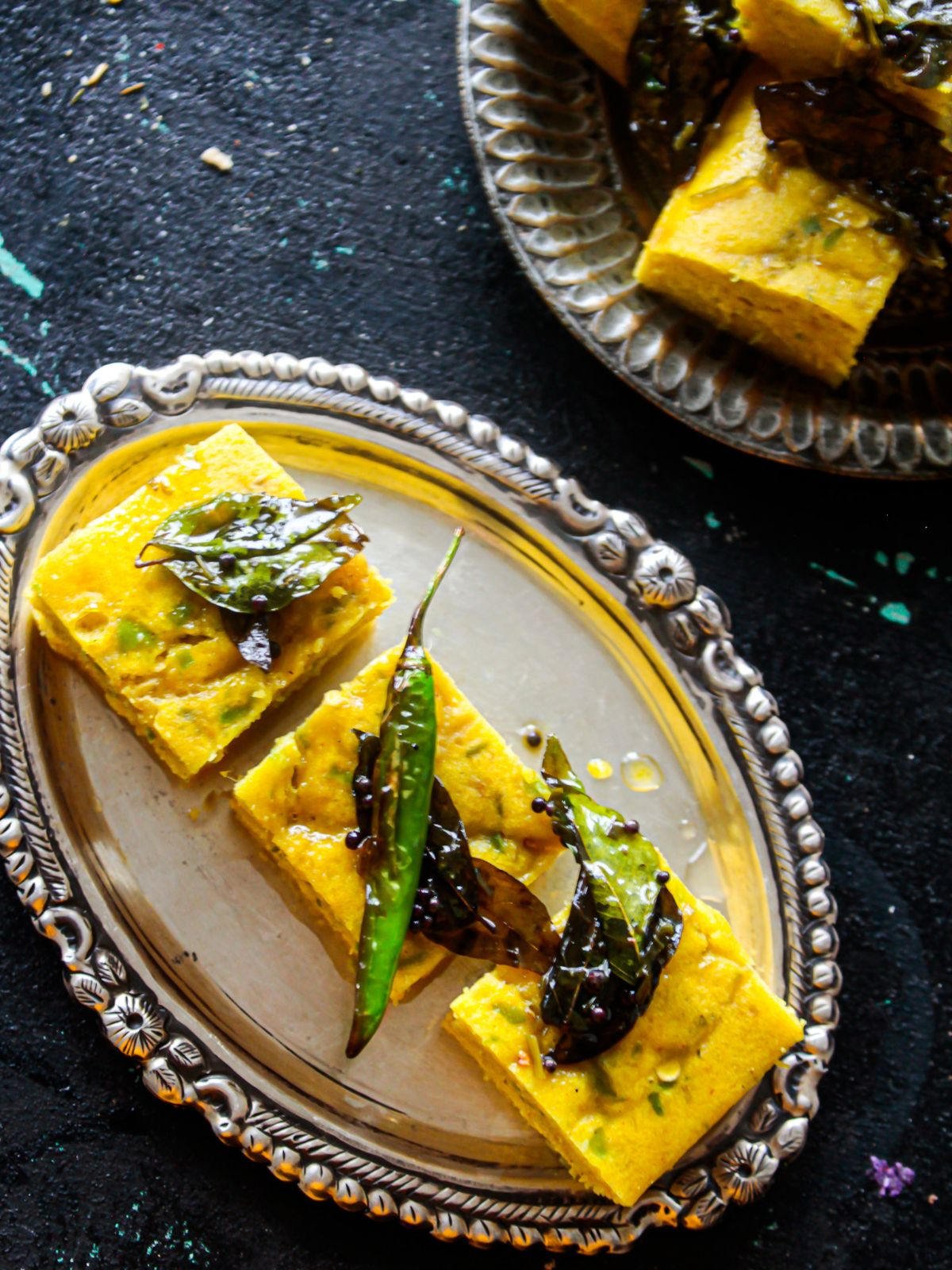 Three slices dhokla on silver platter topped with chili