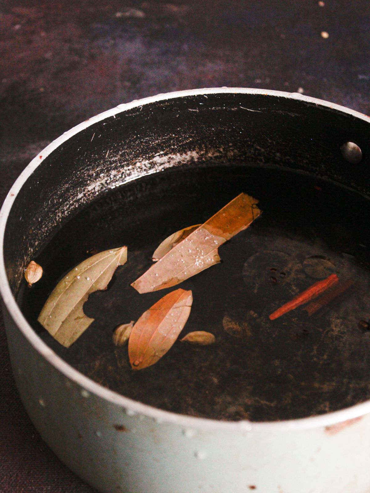 stockpot of water with bay leaf and cinnamon sticks