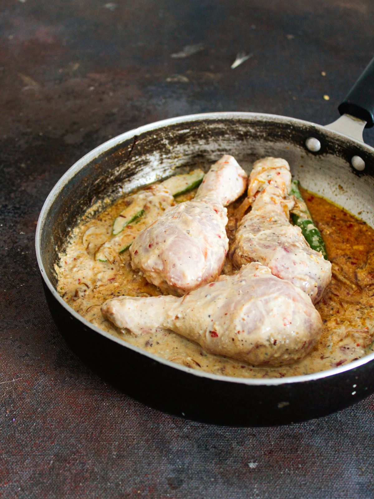 raw chicken legs in sauce in skillet