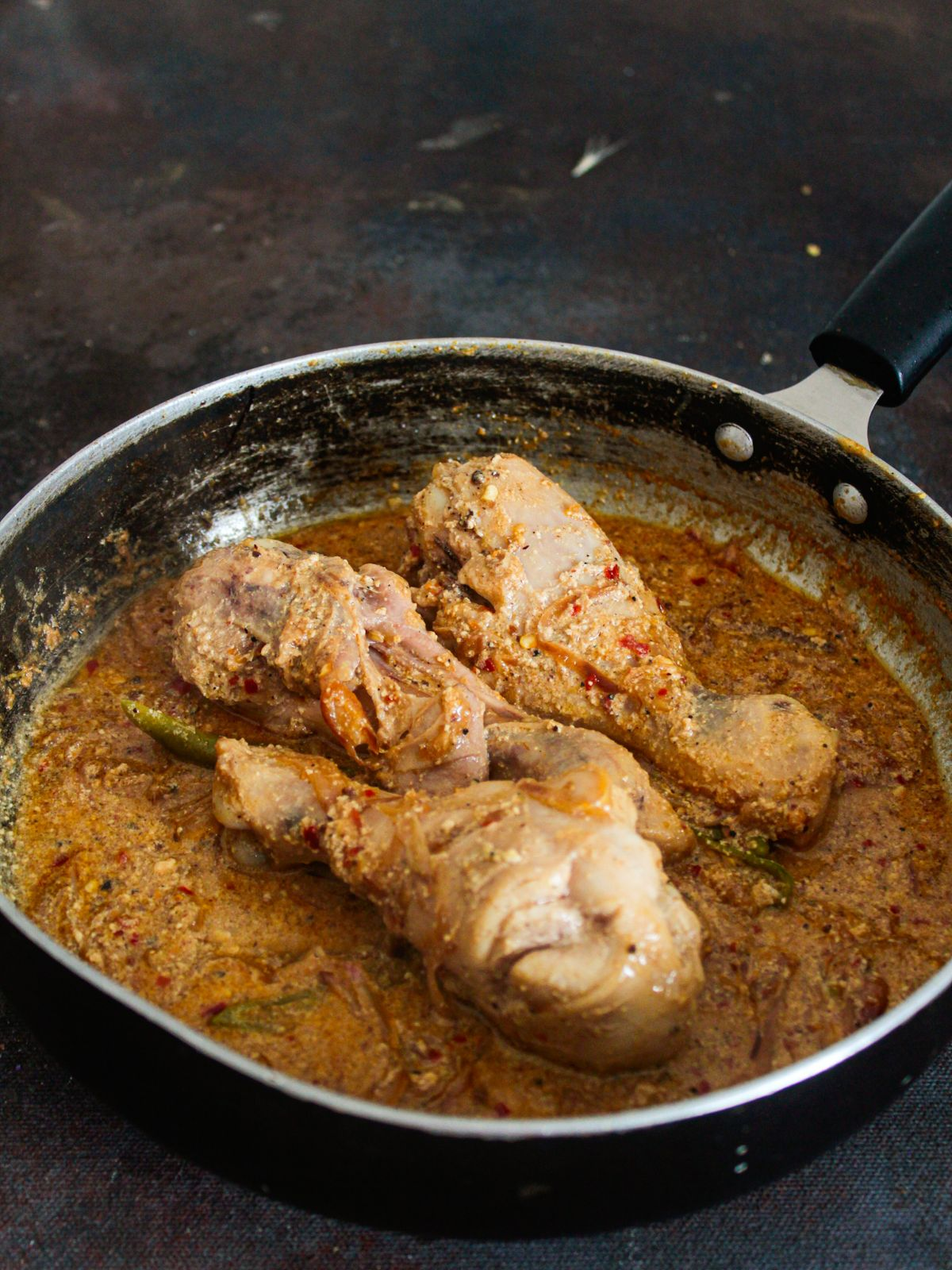 skillet with cooked chicken legs in sauce