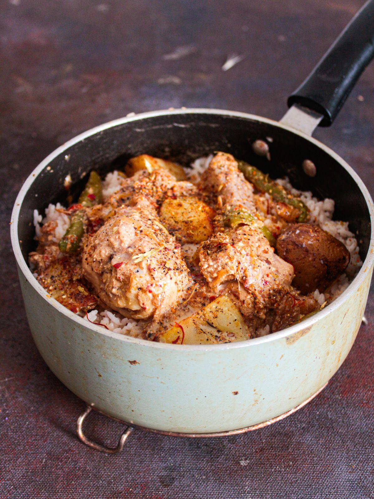 chicken legs on top of rice in saucepan