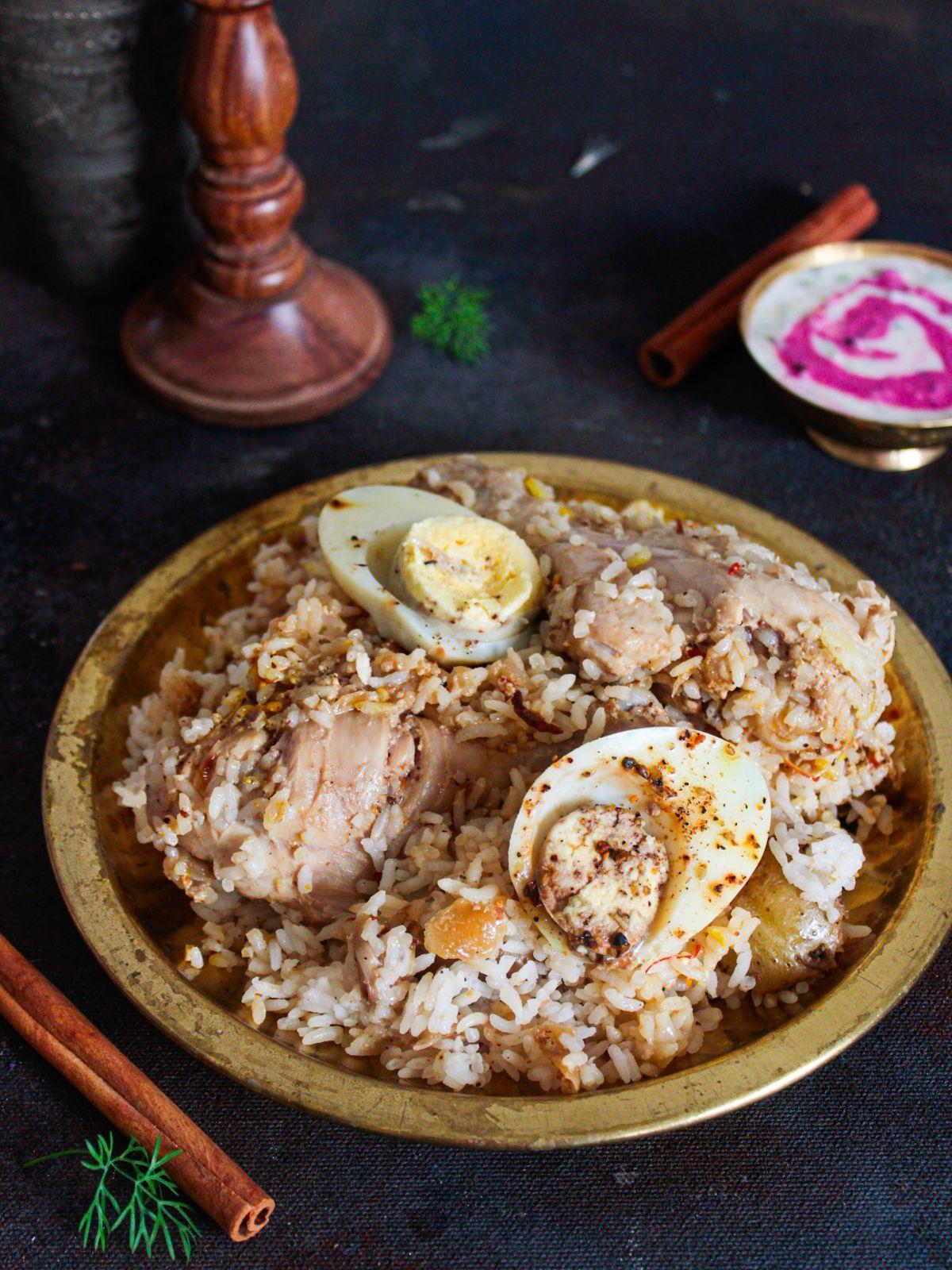 large bowl of biryani on black table by bowl of raita