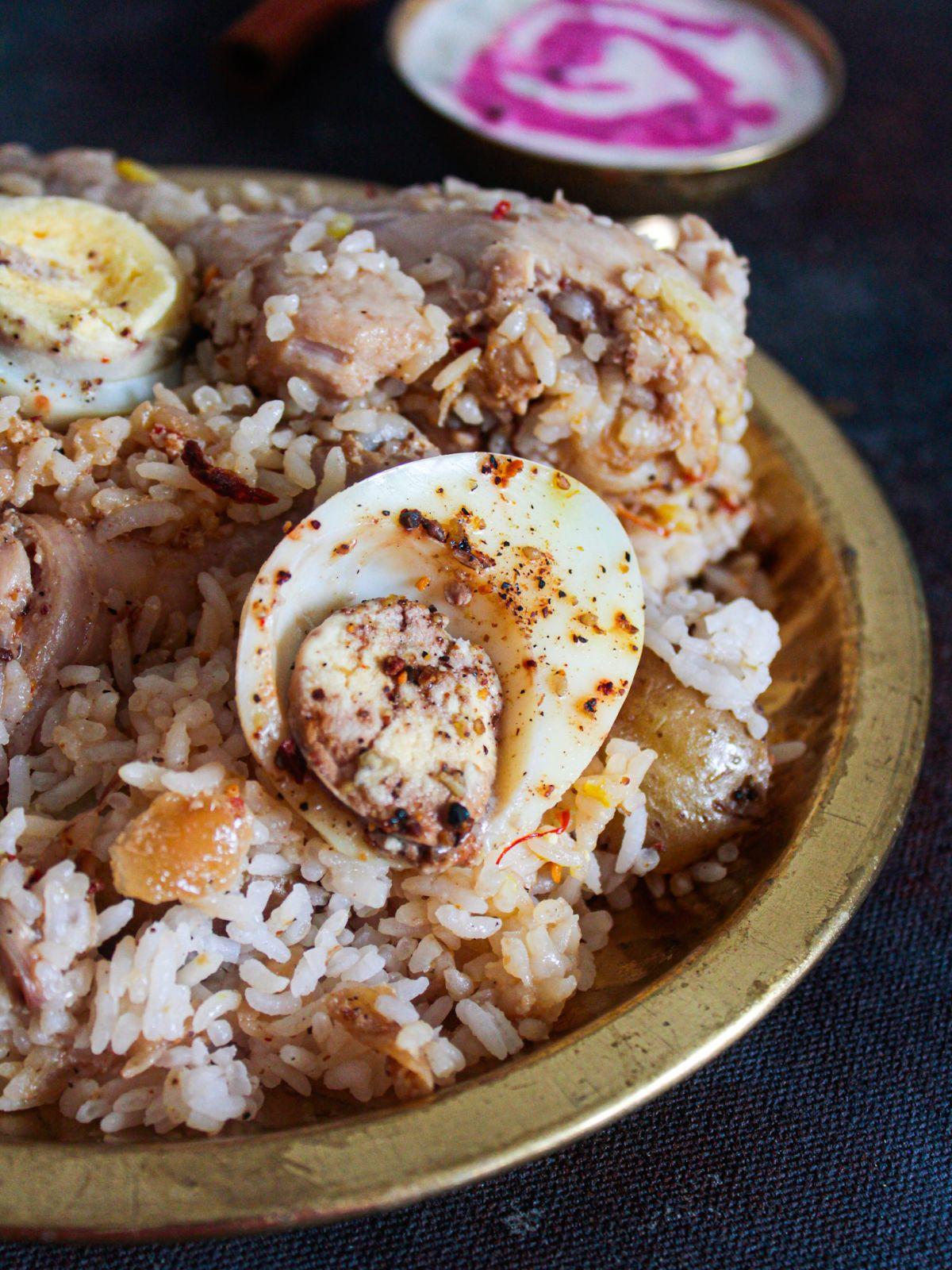 Gold bowl of chicken biryani on black table