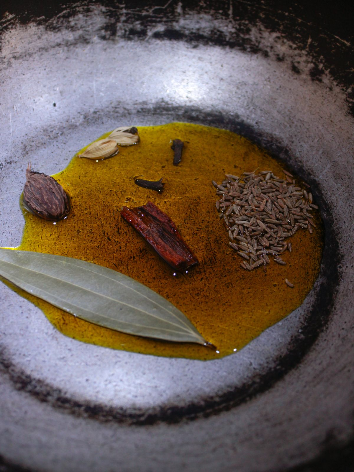 Bay leaf, cinnamon stick, and seed pods in oil in skillet